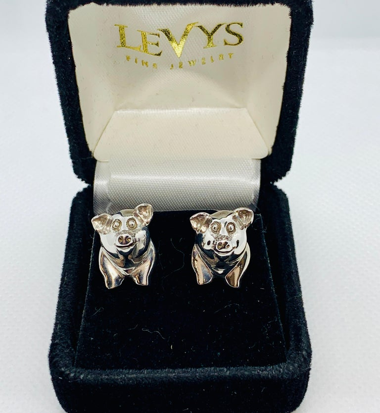 So festive and whimsical set of cufflinks! Made in sterling silver these cufflinks have the pig's smiling head as the front link and the chubby rear with curly tail as the rear link. Set weighs 18.8 grams. The front link / front of the pig measures