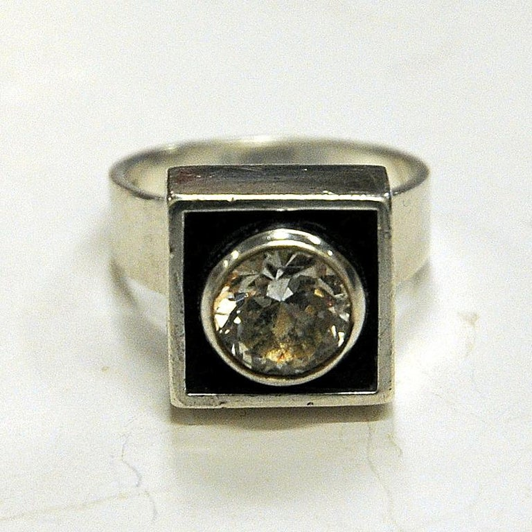 Lovely vintage silvering with a rock crystal brilliant cut stone in the middle by Alton, Sweden, 1968. Clear round stone surrounded by a silver frame on a black surface. Square shape.  Stamped: 935 and Alton S9. Measures: Inner diameter is 16 mm.