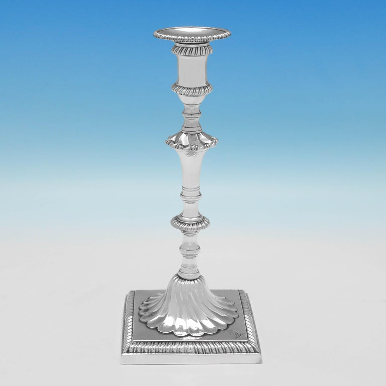 Hallmarked in London in 1767 and 1768 by John Cafe, this exceptional set of four George III, Antique Sterling Silver Candlesticks, are cast, and feature gadroon borders, swirling inverted fluting at the base of the stems and an engraved crest on