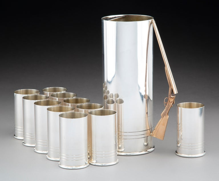 J.E Caldwell & Co, Pennsylvania.  An incredibly stylish and most likely bespoke Sterling silver 12 piece cocktail or drinks set, featuring a pitcher and tumblers resembling shotgun cartridges, the pitcher with a finely-detailed handle in silver