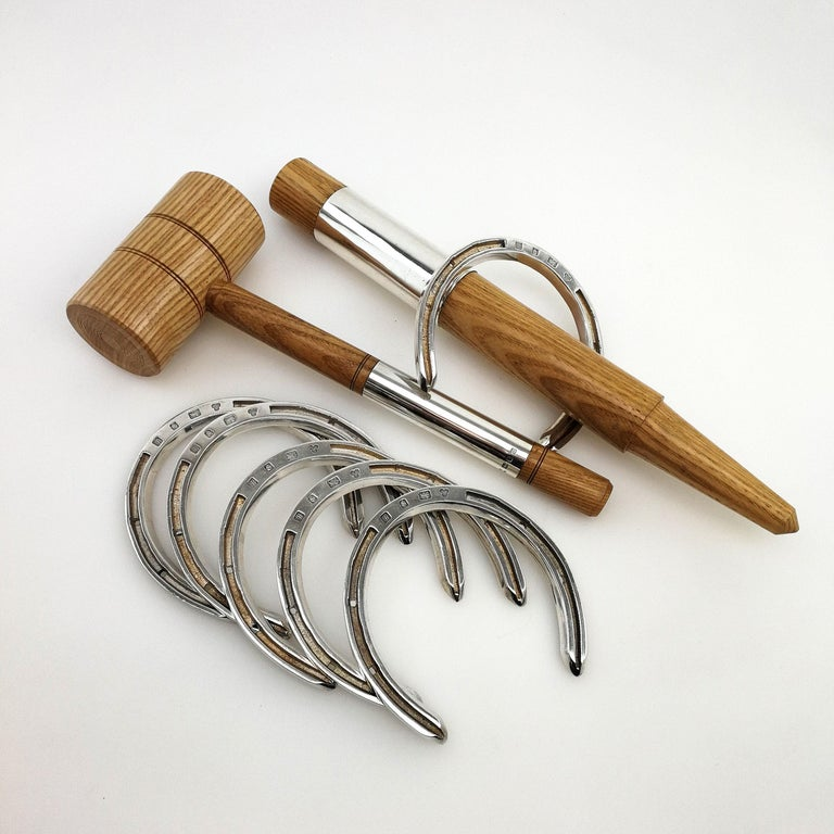 A rare and wonderful sterling Silver and Wood Horseshoes Set. This Traditional Game has been re-imagined in sterling Silver and Wood, with a set of 6 solid Silver Horse Shoes for Tossing, and a light wood Stake & Mallet each with a wide sterling