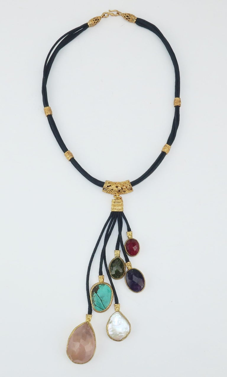 An exotic necklace in braided leather cords laced with filigree sterling fittings with a gold wash all suspending semi precious drops at staggered lengths including rose quartz, mother-of-pearl, turquoise, amethyst and garnet.  Easy byzantine style