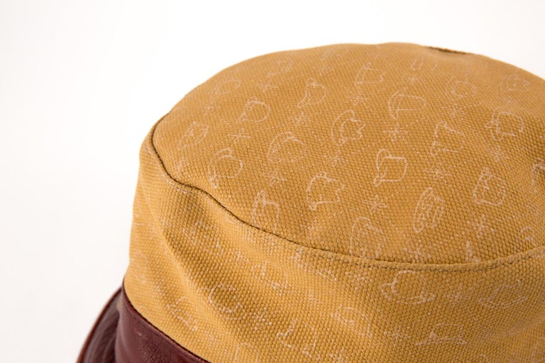 Stetson bucket hat featuring a bordeaux leather border, a camel printed canvas, tarnish gold studs details and a silk lining.  Printed Label Stetson Label size:M Diameter: 21.25in. (54cm) In excellent vintage condition.  Made in Germany. We
