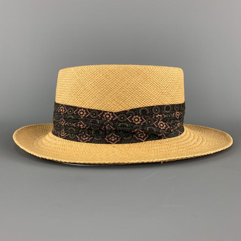 STETSON hat comes in natural woven straw with a navy print gathered stripe.   Very Good Pre-Owned Condition. Marked: (no size)  Measurements:  Opening: 22 in. Brim: 2.25 in. Height: 3.5 in.