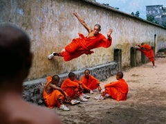 A young monk runs along the wall over his peers at the Shaolin Monastery...