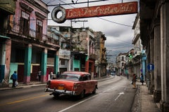 A red car driving through the streets of Havana, Cuba