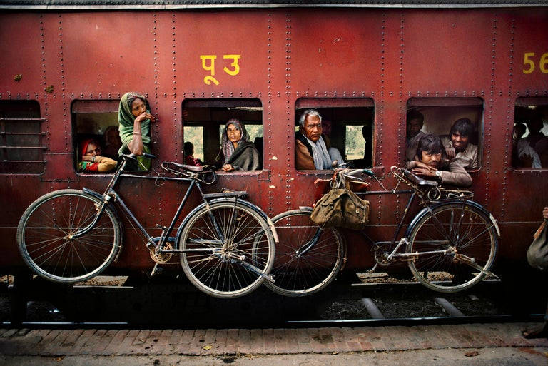 Steve McCurry Color Photograph - Bicycles on Side of Train, India, 1983