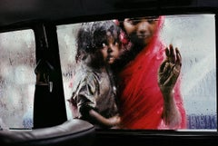 Mother and child looking in through a taxi window, Bombay, India