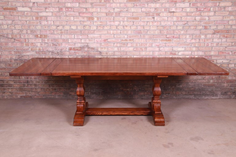 An exceptional Arts & Crafts style solid oak trestle base extension dining table  By Stickley Furniture  USA, late 20th century  Measures: 76