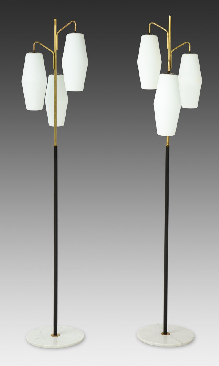Stilnovo pair of floor lamps with three opaline glass lantern shades suspended on gilt lacquer arms and black enameled stems ending on Carrara marble bases, Italy, 1960s. Newly rewired to U.S. standards.  Literature: Thomas Braüniger, Stilnovo: