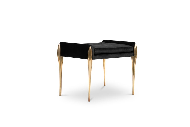Stiletto is a button tufted bench upholstered in velvet. It features brass stiletto legs that are inspired by high heels, providing a sharp and sleek look to your bathroom. It has a rectangular cushioned pad accented by little sloping arms. Feminine