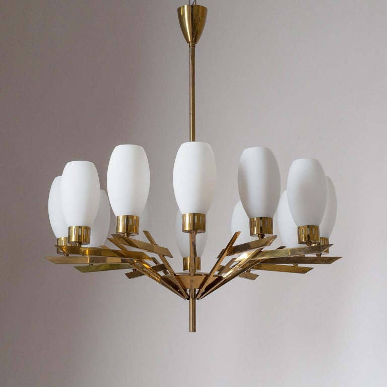 Rare large Stilnovo attributed brass chandelier from the early 1960s. Twelve articulated brass arms each with a blown satin glass diffuser. Fine original condition with a nice patina on the brass. Original E14 sockets with new wiring. Height without