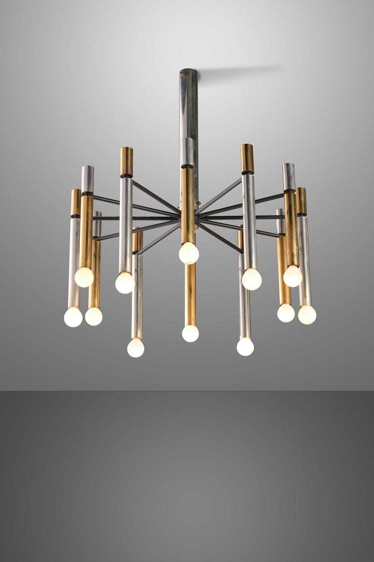 Sculptural 12-light Stilnovo chandelier with alternating brass and aluminum tubular arms suspended from black enameled aluminum structure. A unique masterpiece in lighting design with striking combination of gold, silver and black and the magical