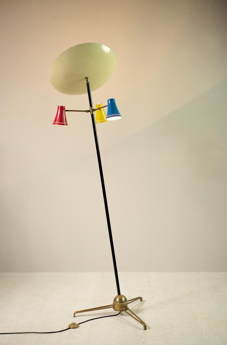Tripod floor lamp in lacquered metal and brass, Stilnovo 1950. The black lacquered shaft rests on a heavily leaded sphere allowing the tilt to be adjusted. Three arms of lights adjustable by a ball and socket head receive polychrome blue, yellow and