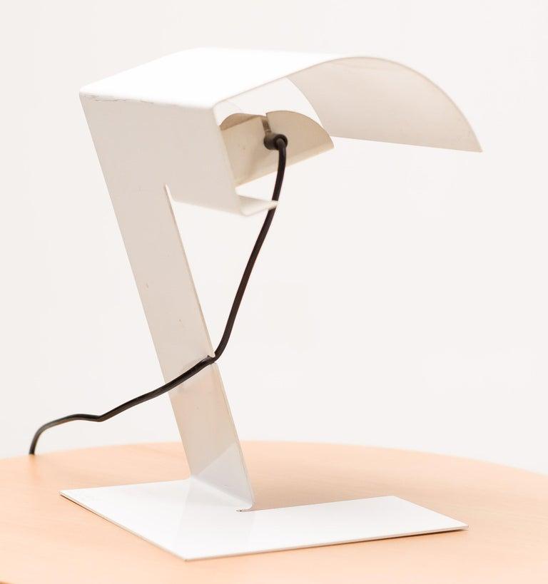"A ""Bliz"" table lamp for Stilnovo, designed by Trabucchi & Vecchi & Volpi for Stilnovo.  White lacquered sheet metal, with impressed mark STILNOVO/Milano-Italy. Wired for use in the USA. Lit. Repertorio, 1972, p. 375."