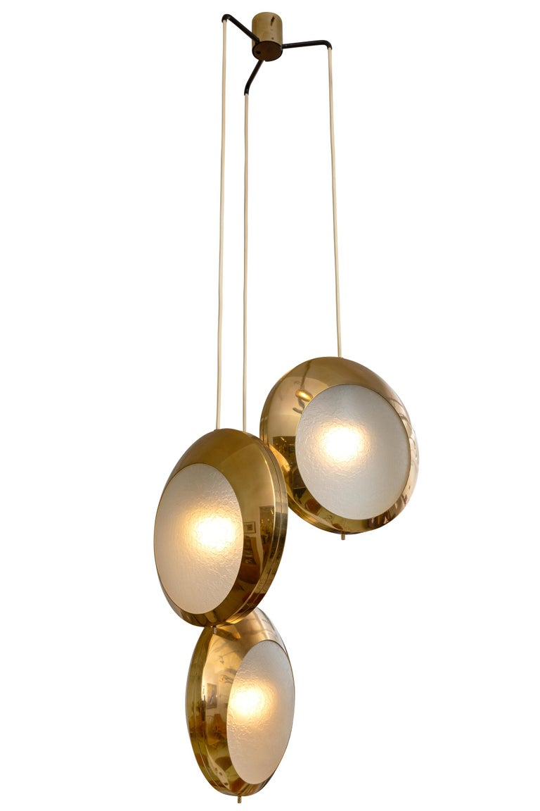 A rare and striking three pendant light by Stilnovo. The glass has a wonderful textured surface that diffuses the light creating a lovely effect. The height can easily be adjusted up or down by changing the length of the cords.