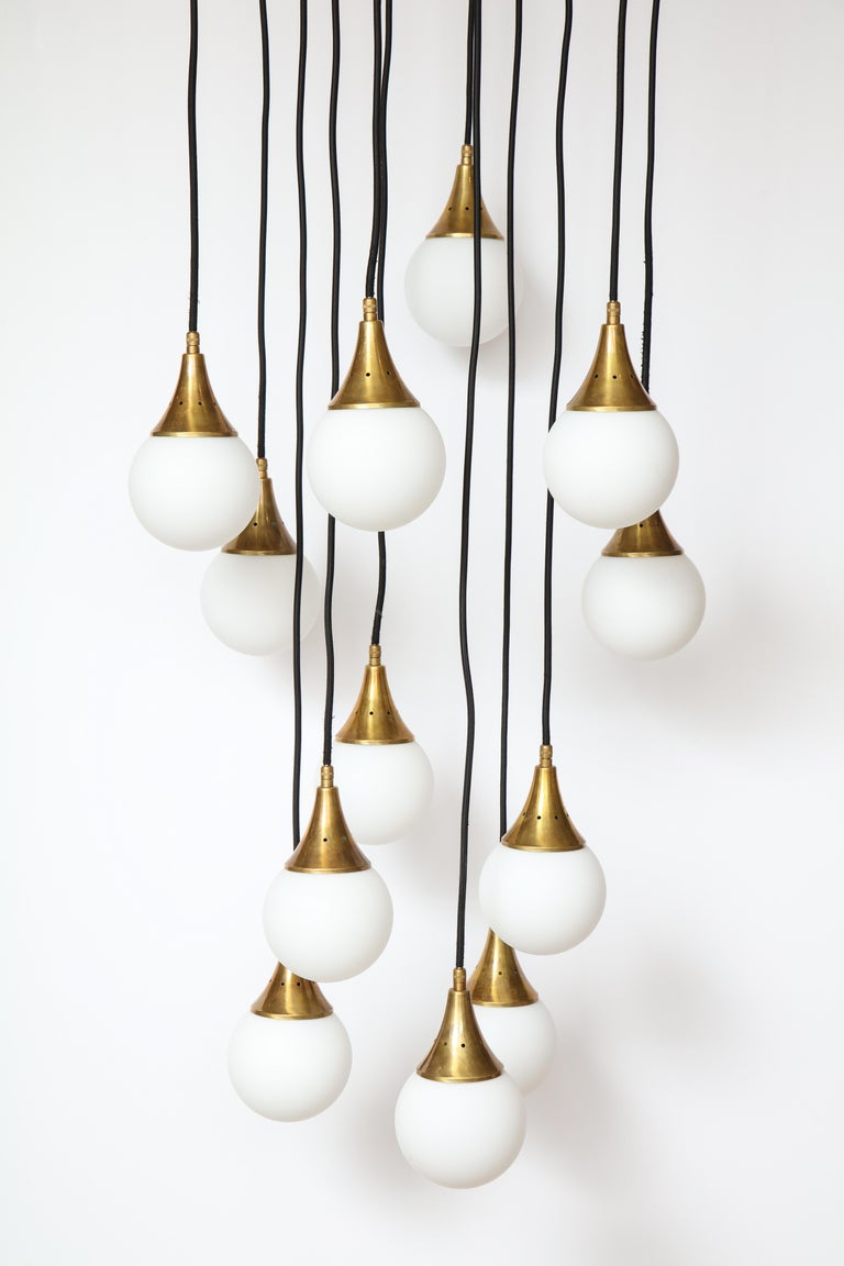 Stilnovo cascading chandelier with twelve opaline glass ball lights supported by brass canopies and suspended by adjustable black fabric wiring. The glass lighting can be adjusted via the fabric wiring to various height levels. The whole supported