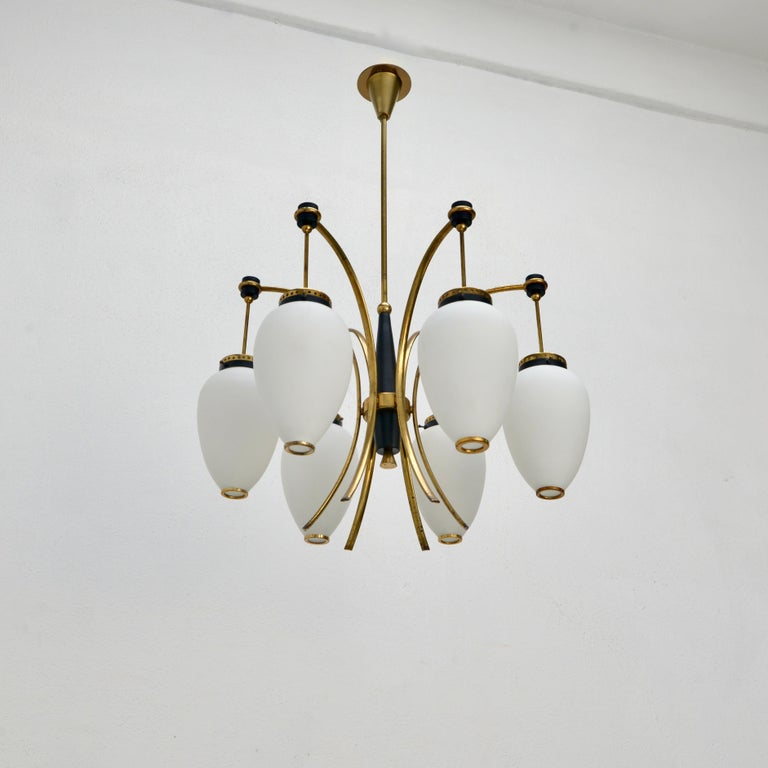 Stilnovo of the period mid century Italian 6 globe 1950s naturally aged brass chandelier with hand blown glass shades. Wired with 1-E12 candelabra based sockets (1) per globe shade (6 in total). Wired for use in the US. Light bulbs included with