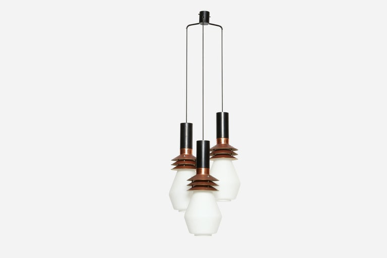 Stilnovo chandelier model 1253 Copper, enameled metal, matte glass. Three very large glass bells suspended on black cords. Rare fixture with Stilnovo label. Body of the pendants is 20.5 inches in height and 8 inches in diameter, Italy, 1960s.