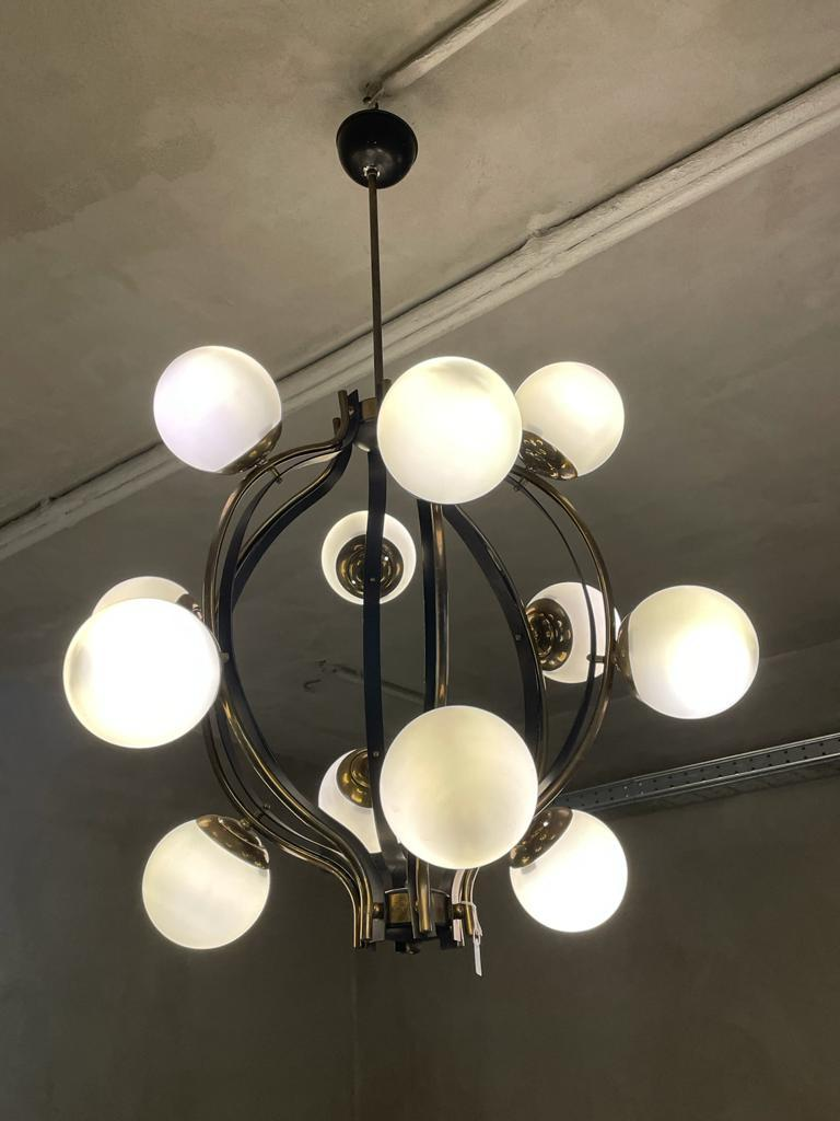 Chandelier manufactured by Stilnovo in Italy, 1960. Structure in polished brass and black lacquered metal. It has twelve opaline satin glass balls. The structure has six curved bars of brass and black lacquered metal, each of which precisely has
