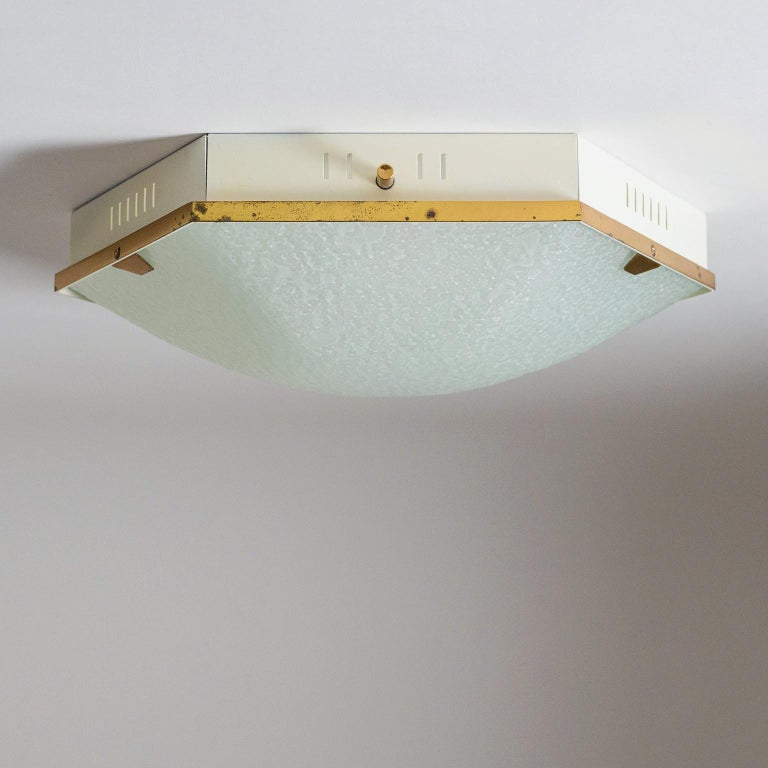 Superb hexagonal flush mounts by Stilnovo, early 1960s. An off-white lacquered metal body with vertical perforations with a curved and textured glass diffuser and brass rim and details. These are in very good original condition with a nice patina on