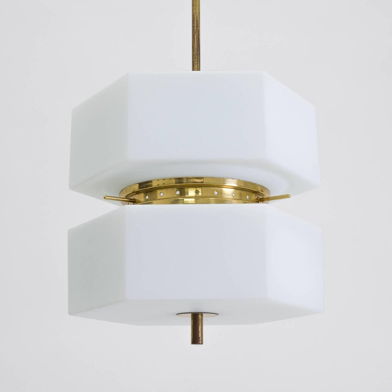 Very unique Stilnovo attributed pendant with two hexagonal satin glass diffusers and brass hardware from the 1950s. The glass bodies are made of 'triplex opal glass' which has an opaline central layer with clear casing on either side each with a