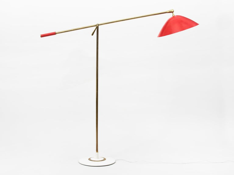 Elegant, adjustable midcentury brass floor lamp with bright red lacquered perforated metal shade and handle. The body of the lamp features beautifully rendered solid brass parts and twin brass stems. Manufactured in Milan in the 1950s by Italian