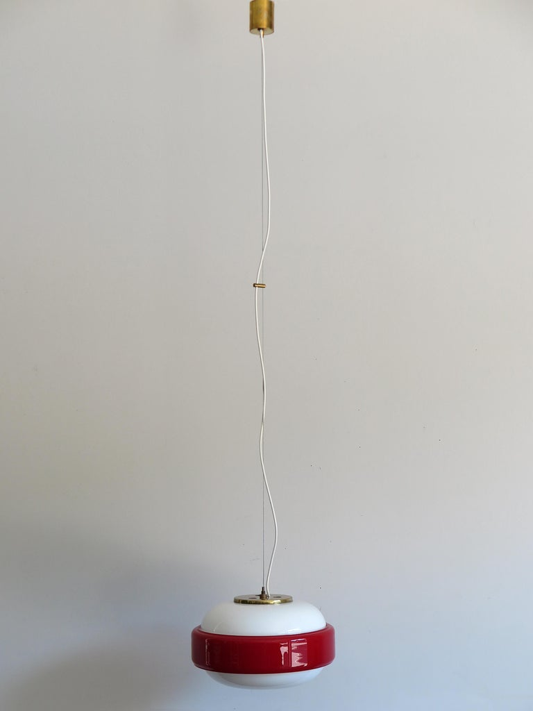 Italian amazing pendant lamp or hanging light produced by Stilnovo from 1960; brass, white opaline glasses and incamiciato red glass; original Stilnovo label, circa 1960s.  Please note that the lamp is original of the period and this shows normal