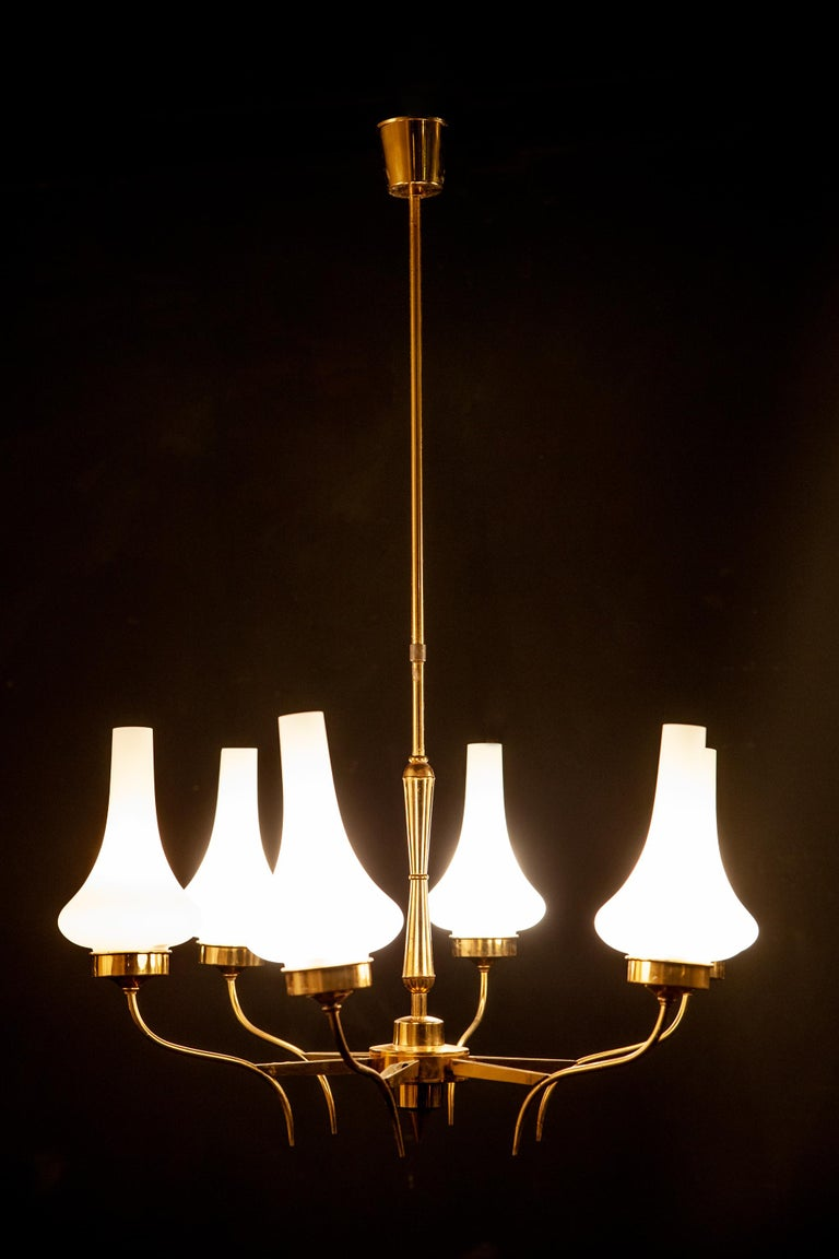 Linear elegance, brass six arm chandelier, holding upturned opaline glass shades. Excellent vintage condition. Six E 27 light bulbs. The rod can shortened on request.