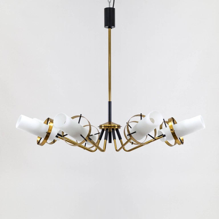 Excellent brass Sputnik chandelier attributed to Stilnovo with eight arms and satin glass diffusers, 1950s. The hardware is made entirely of brass, partially lacquered in black. Each arm ends in a