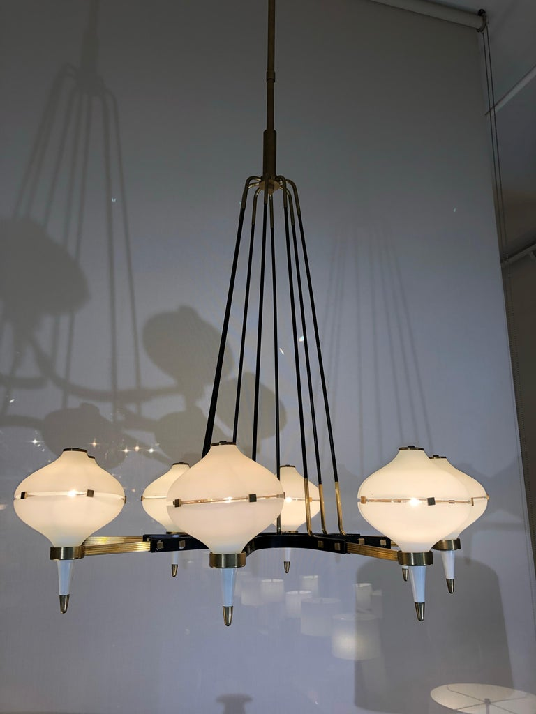 A modernist eight-light chandelier attributed to Stilnovo. Patinated brass, black enamel and frosted glass. Fully rewired and restored.