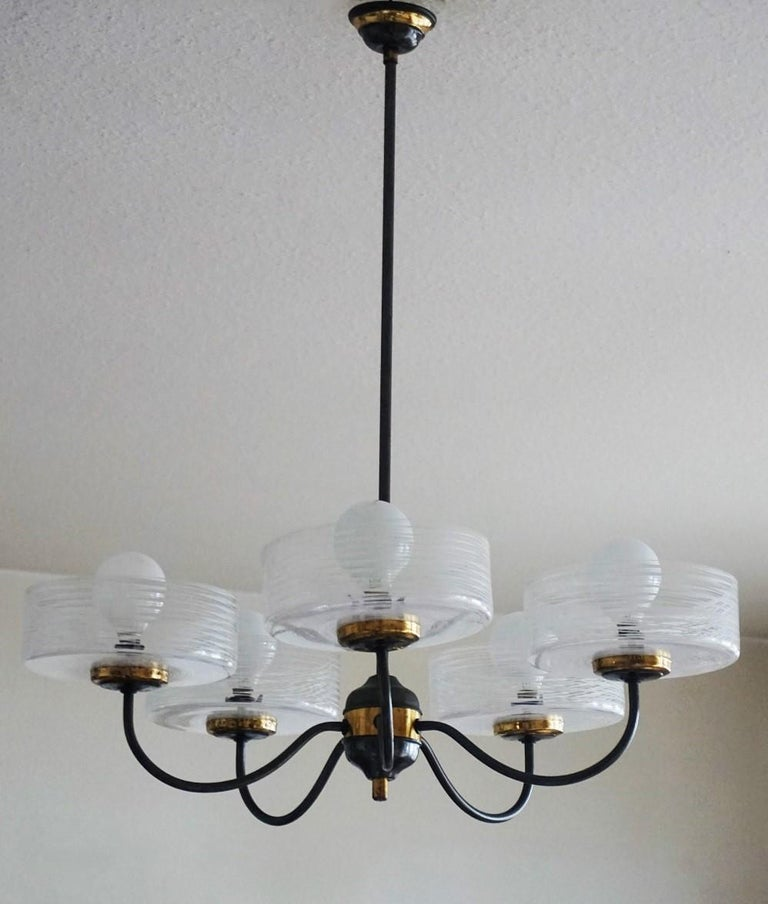 A Stilnovo brass parcel patinated five-light chandelier with large Murano glass shades in modernist clear lines design, Italy, 1950s. The glass globes are in very good condition, brass with some wear and aged patina, rewired. Measures: Height 27