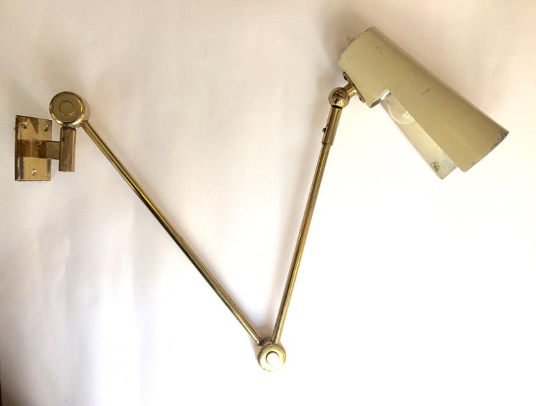 An original brass and enameled metal wall lamp, adjustable arm. Edited by Stilnovo. Stamped.