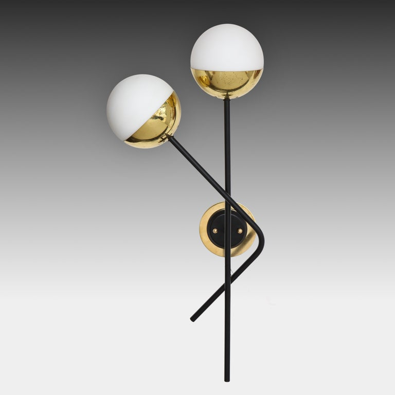 Stilnovo modernist pair of two-light sconces with opaque or frosted glass shades held in brass fittings suspended on black painted metal rods. These architectural wall lights are a classic Stilnovo design with striking contrasting signature colors