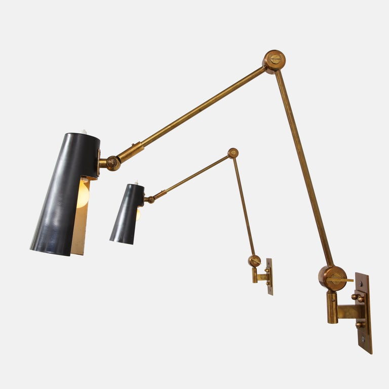 Stilnovo pairs of articulating wall lights model 2024 with original black enameled perforated metal shades on brass arms, Italy, 1950s. The metal shades pivot from ball joints and the articulating arms are adjustable from butterfly keys. Beautifully