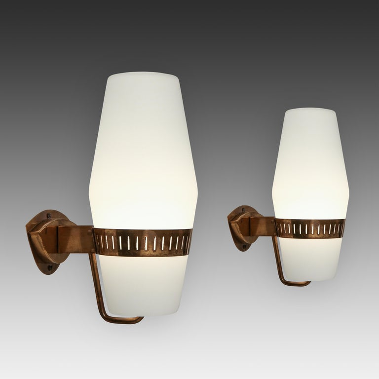 Stilnovo set of four elegant sconces model 2078 with large frosted glass lantern-shaped shades held by brass brackets. Recently rewired to U.S. standards with custom shaped backplates to fit original backplates.  Priced per pair.  Literature: