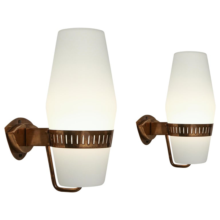 Stilnovo set of four or pairs of elegant sconces model 2078 with large frosted glass lantern-shaped shades held by brass brackets. Recently rewired to U.S. standards with custom shaped backplates to fit original backplates in keeping with its