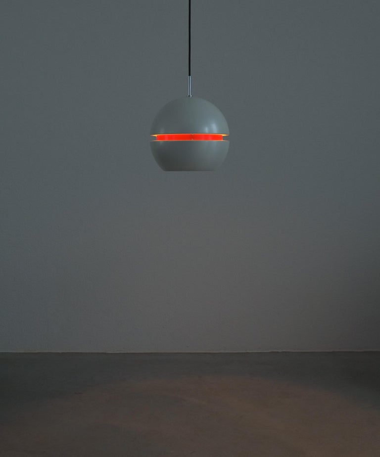 Stilnovo pearl white red globe pendant lamp, circa 1965  Beautiful Italian pendant light, aluminium sheet, enameled pearly white and red with a visor effect once illuminated. It's in good condition with no major damages and hardly to the original