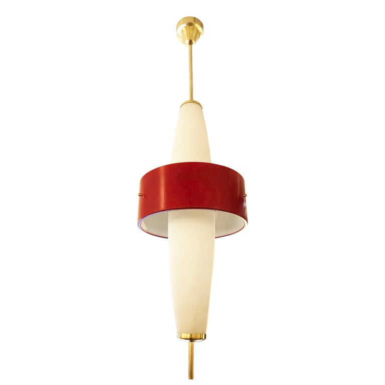 Stilnovo pendant with two elongated frosted glass shades and a central red aluminum ring. Brass hardware and fittings. Holds six candelabra sockets. Height of stem can be adjusted as needed.  Condition: Excellent vintage condition, minor wear