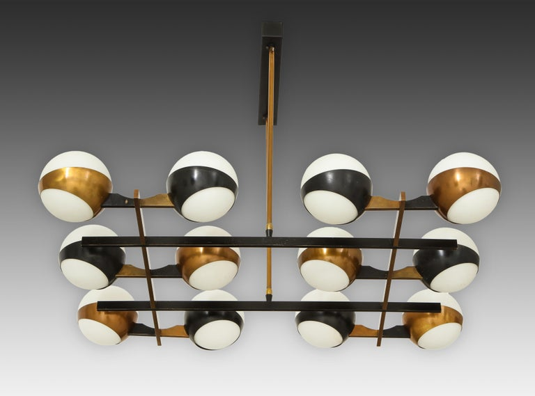 Stilnovo chandelier with twelve-opaque glass globes held in brass rings with alternating rings painted black on architectural grid-like structure. The structure is suspended by two brass rods on a black painted rectangular metal canopy. This