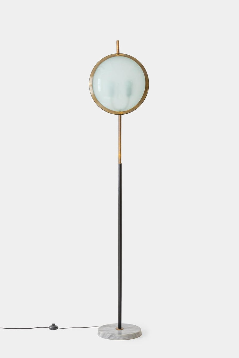 Stilnovo very rare floor lamp with convex glass shades on each side of brass and lacquered metal circular frame with brass finial, suspended on brass and black enameled stem on circular marble base. Chic and iconic Stilnovo design and rarely seen on