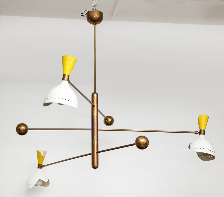 Stilnovo rare three-arm mobile chandelier suspended from brass structure and canopy, Italy, circa 1960. This hanging light fixture has rotating arms with curvaceous double cutout aluminum shades in lacquered white and yellow enamel and brass