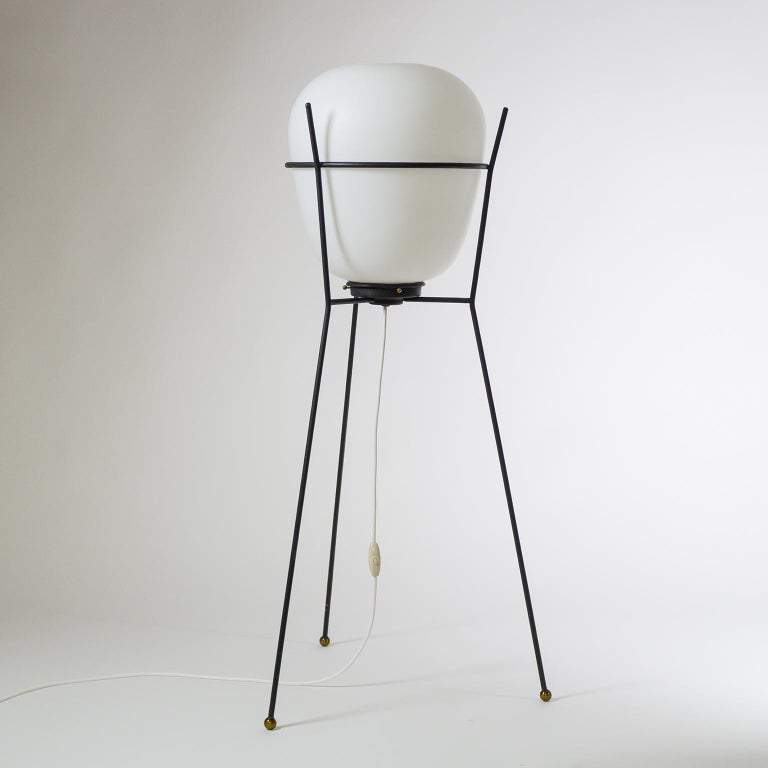 Modernist Stilnovo tripod floor lamp 1950s. A sculptural minimalist blackened steel structure with brass details holds a large oval satin glass (triplex opal) diffuser. One original brass and ceramic E27 socket with new wiring.