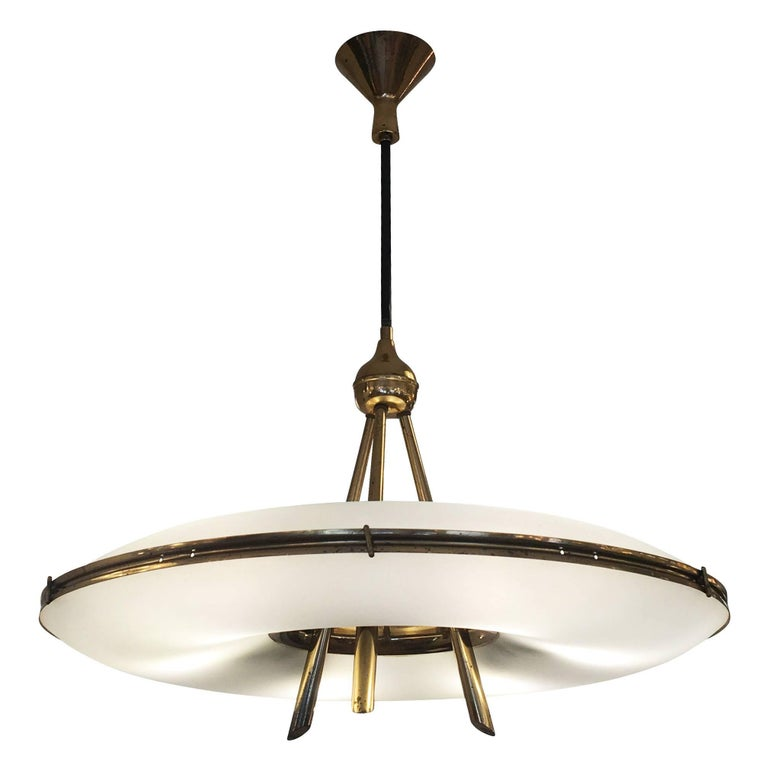 Saucer shaped chandelier by Stilnovo with two frosted glass shades on a brass frame. The architectural and well thought out design is highlighted by the three stems that merge into one and the contoured canopy. Holds six candelabra sockets. Height