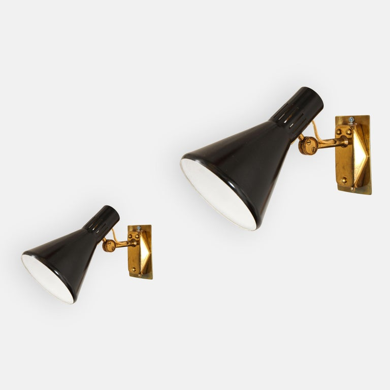 Stilnovo set of six articulating sconces with black lacquered perforated metal shades which pivot vertically on brass arms attached to original backplates. Retains original manufacturers label marked STILNOVO. Recently restored and rewired to U.S.
