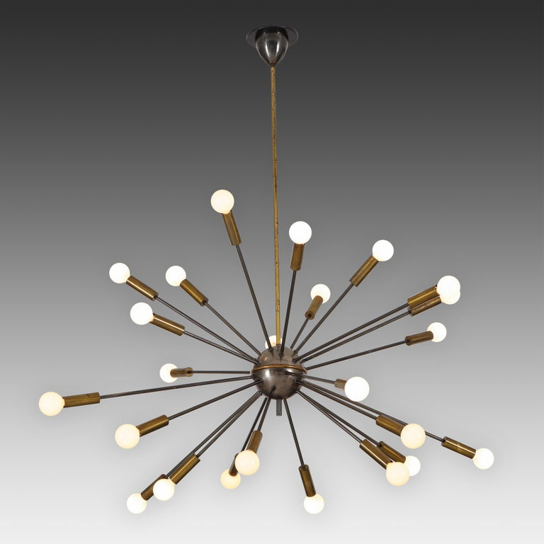 Stilnovo rare original sputnik chandelier from 1950s, Italy. This extraordinary 24-light sputnik ceiling light is composed of brass and black lacquered tubular metal arms which radiate on an aluminum globe structure with central brass ring and lower
