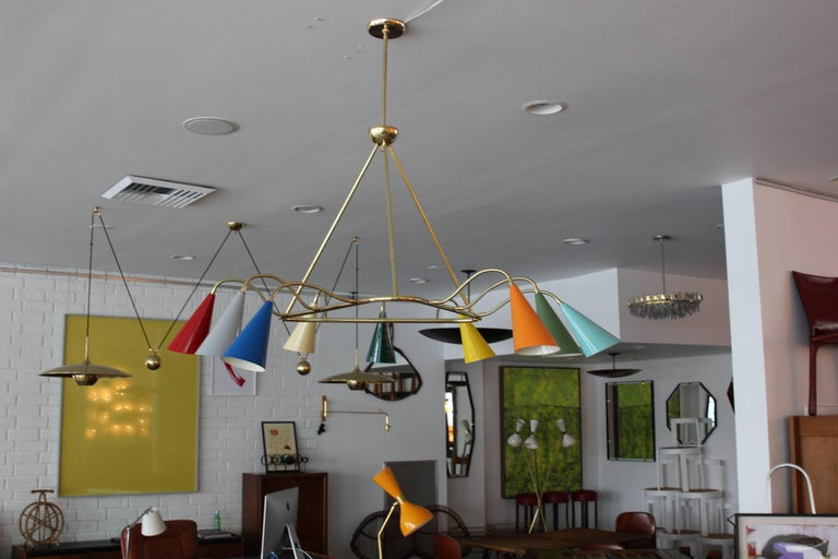 Stilnovo style pendant with nine multicolored cones on adjustable brass arms.