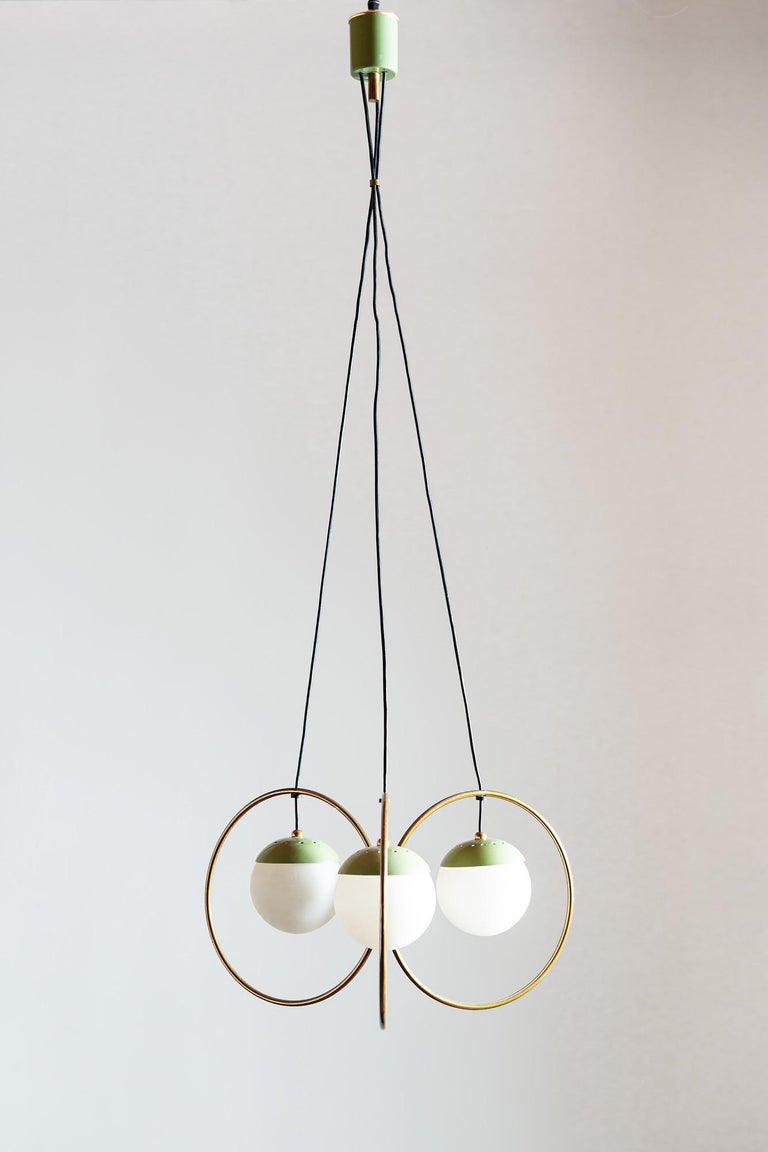 Rare three ball chandelier in brass with green enamel accents and opaque glass globe diffusers. In the style of Stilnovo, Italy, 1950s.