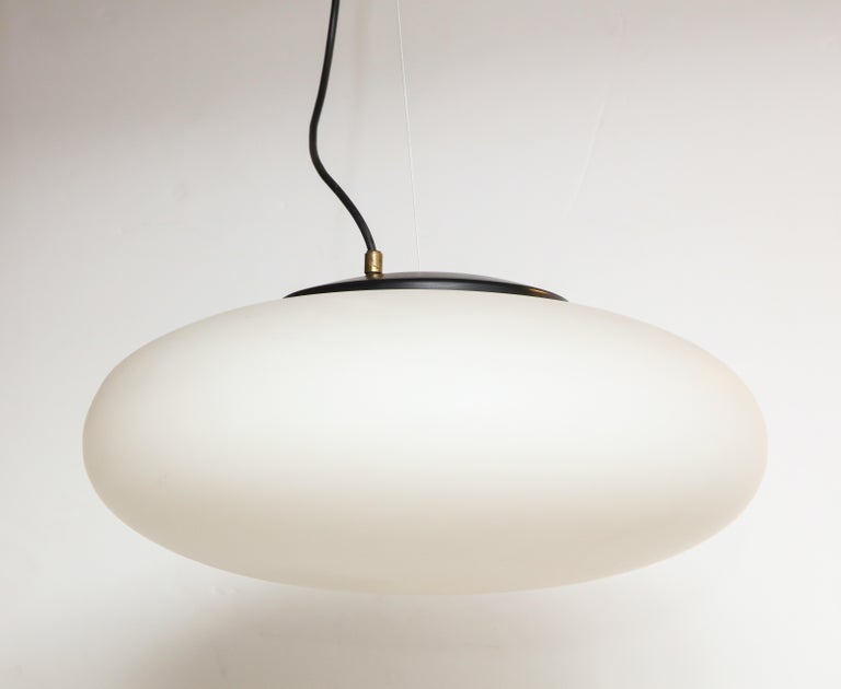 "Stilnovo suspension light/chandelier, Italy, circa 1950s-1960s Metal, brass, white opaque milk glass  Measures: H 31 (Drop adjustable), diameter 18 in. (H of globe: 5-6"")."