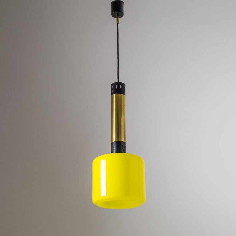Classic Stilnovo pendant with yellow glass diffuser from the 1950s. The hardware is tubular brass with perforated black lacquered aluminum details. Fine original condition with some patina on the brass. One original brass and ceramic E27 socket with